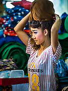 "30 JANUARY 2016 - NONTHABURI, NONTHABURI, THAILAND: A woman puts on her ornate wig before a ""likay"" show at Wat Bua Khwan in Nonthaburi, north of Bangkok. Likay is a form of popular folk theatre that includes exposition, singing and dancing in Thailand. It uses a combination of extravagant costumes and minimally equipped stages. Intentionally vague storylines means performances rely on actors' skills of improvisation. Like better the known Chinese Opera, which it resembles, Likay is performed mostly at temple fairs and privately sponsored events, especially in rural areas. Likay operas are televised and there is a market for bootleg likay videos and live performance of likay is becoming more rare.     PHOTO BY JACK KURTZ"
