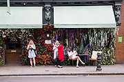 Women outside The Ivy Chelsea Garden on Kings Road, use their mobile phones on 24th May 2017 in London, United Kingdom.  From the series Our Small World, an observation of our mobile phone obsessions
