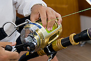 Close up of angler's hands applying extra drag on gold reel of angler in fighting chair.