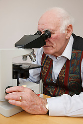 Elderly man looking through microscope.