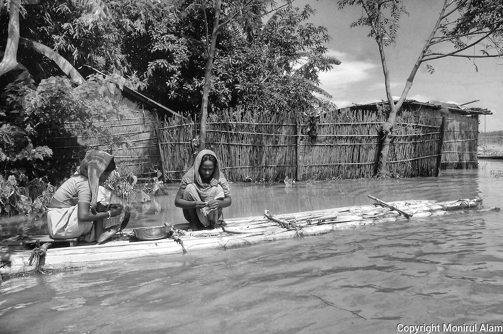 Sirajgonj. Bangladesh. Women preparing food next to their house affected by a flood. The boat is self-made. Bangladesh ranks first as the nation most vulnerable to the impacts of climate change. Scientists expect rising sea levels to submerge 17 percent of Bangladesh's land and displace 18 million people in the next 40 years.