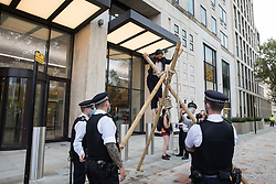 London, UK. 10 November, 2020. An environmental activist from Extinction Rebellion descends from a tripod outside the Shell Centre at the end of an event to mark the 25th anniversary of the killings of the Ogoni Nine. The Ogoni Nine, leaders of the Movement for the Survival of the Ogoni People (MOSOP), were executed by the Nigerian government in 1995 after having led a series of peaceful marches involving an estimated 300,000 Ogoni people against the environmental degradation of the land and waters of Ogoniland by Shell and to demand both a share of oil revenue and greater political autonomy.