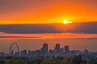 A partially eclipsed sun sets over the skyline of Saint Louis, Missouri. About 40 minutes before the sun set, it moved behind some thick clouds to the west. There was a small gap in between clouds, but it kept getting smaller. As the sun sank lower, the gap wasn't big enough to fit the entire disk of the sun. So I just shot the upper portion of the sun where the moon was. I had to time it just right, because this lasted only a few seconds. The sun looked like it would appear one more time, but it never did. <br /> To see the sun setting over the city skyline, I had to find a location a few miles northeast of the city, with enough height to see over the trees. The 100 foot high mound at Cahokia Mounds turned out to be the perfect place. 100 feet may not seem very high, but this mound was built entirely by hand over 1,000 years ago by an ancient Indian civilization. The base is as wide as the Great Pyramid of Giza and it took hundreds of years to build by hauling baskets of soil and clay. Dozens of mounds in the area are preserved as a UNESCO World Heritage Site.