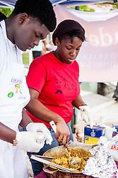 "Kerish ""Chef K"" Robles, right, serves Smoky Caribbean Jambalaya with Damian Fregiste.  Coal Pot Cook-Off  at Emancipation Garden raising funds for St. Thomas Historical Trust.  St. Thomas, VI.  19 May 2015.    © Aisha-Zakiya Boyd"