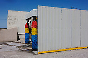 Car wash brushes await business on a motorway services forecourt near Paradas, Andalucia, Spain. Alongside the A 92 motorway near Paradas, the service station is a stopping place on the main highway between the Andalucian cities of Granada and Seville and is around the back of the main petrol facility. The saturated colours of the red, yellow and blue brushes contrast the otherwise grey tones of the metal sheeting and concrete.