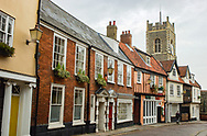 The back streets of Norwich in Norfolk with church spire and traditional architectural designs.
