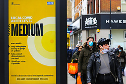 © Licensed to London News Pictures. 16/10/2020. London, UK. A woman wearing a face covering in north London walks past the government's latest COVID-19 advert informing about the tier two restrictions, as London moves to COVID-19 tier two restrictions from tonight, following the government's announcement of tougher measures in the capital to manage increasing cases. From midnight tonight, households in London will not be allowed to mix indoors, including in pubs and restaurants.  Photo credit: Dinendra Haria/LNP