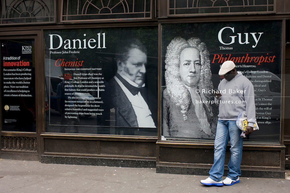 Beneath the portraits of scientist Professor John Thomas Daniell and philanthropist Thomas Guy, a London commuter waits for a bus outside King's College London university in the capital's Strand