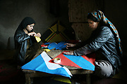 Marzia, the first wife, at right, and her second daughter, Noyi, 18, of Noor Agha, about 52,  make a kite together in the house, Kabul, Afghanistan, Tuesday, March, 13, 2007. Noor Agha is a renowned kite maker who made kites for the movie makers of the best-selling novel, The Kite Runner, which will be distributed by Dreamworks and Paramount Vantage in Nov. this year. Noor Agha's wives, using their special glue, help him produce enough kites to please the clients' needs. Some of his children can also make their own kites with plastic bags and bamboo sticks. As the Afghan New Year's Day (Nawruz) approaching on March 21, the finger tips of Noor Agha's family got busier for mass production.