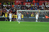 Swansea's Wayne Routledge shows his dejection as Arsenal players celebrate their 2nd goal. Barclays Premier league, Swansea city v Arsenal at the Liberty Stadium in Swansea on Saturday 28th Sept 2013.  pic by Andrew Orchard, Andrew Orchard sports photography.