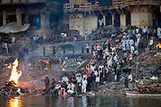 Body bathed in River Ganges and traditional Hindu funeral pyre cremation, Manikarnika Ghat, Holy City of Varanasi, India