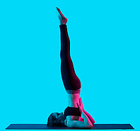 one caucasian woman exercising yoga exercices Sarvangasana  in silhouette studio isolated on blue background