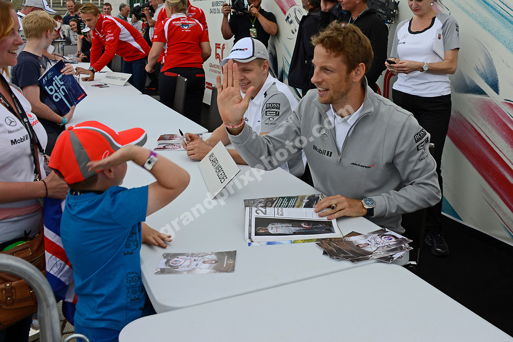 Jenson Button and Kevin Magnussen (both McLaren-Mercedes)  signing autographs during 2014 British Grand Prix at the Silverstone. Photo: Grand Prix Photo