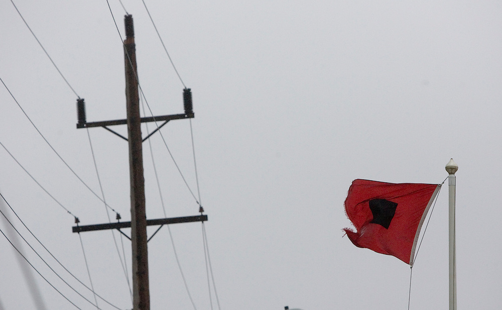 """(PPAGE1) Sea Bright 9/2/2006   A """"Storm Warning"""" flag flies on a flag pole adjacent to a home on Ocean Avenue in Sea Bright.   Michael J. Treola Staff Photographer.....MJT"""