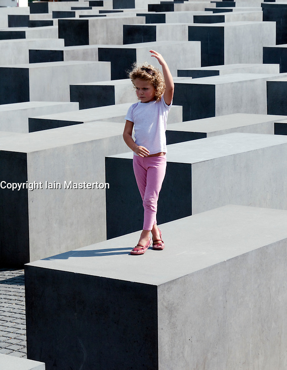 young girl posing on top of concrete blocks at the Memorial to the Murdered Jews of Europe in central Berlin Germany 2008