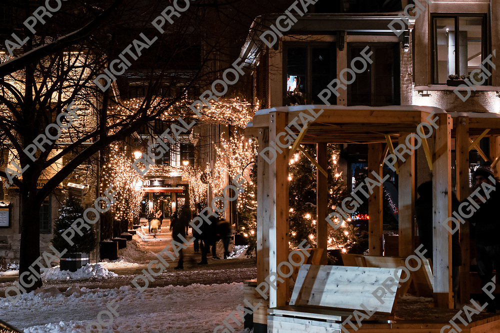 Montreal, Quebec, Canada - January 3, 2021 Rue Saint Amable during winter night with traditional christmas lights and snow with unrecognizable and blurred people viewed from Place Jacques-Cartier in Montreal Old Port