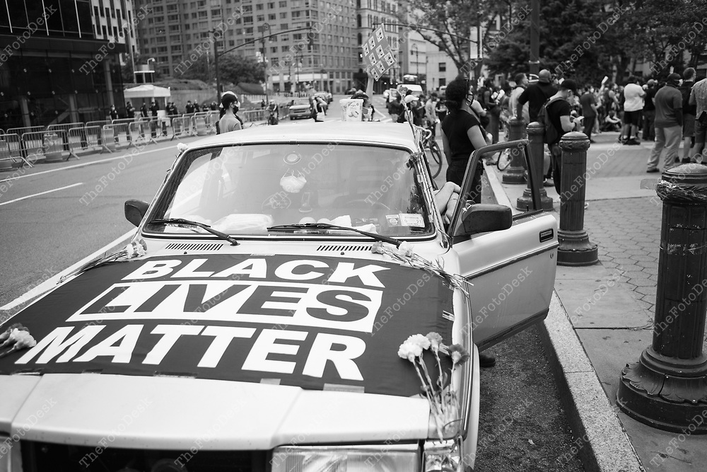 NEW YORK, NEW YORK:  BLM demonstrators lace a car with a BLM flag and flowers during a rally at the Triumph of the Human Spirit Sculpture at Foley Square in New York on Thursday June 11, 2020. Day 17 since the killing of George Floyd by Minneapolis, Minnesota Police officer Derek Chauvin.  (Brian Branch-Price/TheFotoDesk.)