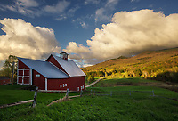 Late day light and amazing cumulous clouds over Stowe Pinnacle and the Granfeld Barn in Stowe, Vermont USA