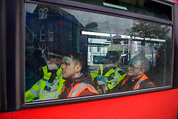 """© Licensed to London News Pictures. 27/10/2021. London, UK. Police sit next to detained people on a London bus to be transported to a police station after protesters from climate campaign 'Insulate Britain', an offshoot of Extinction Rebellion (XR), blocked traffic on the A40 Western Avenue in Acton. Following a national injunction covering England's highways, Insulate Britain declared the M25 """"a site of nonviolent civil resistance"""" vowing to return to the motorway network to continue their protest action. Photo credit: Peter Manning/LNP"""