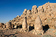 Statue heads, from right, Herekles, Apollo & Zeus, with headless seated statues in front of the stone pyramid 62 BC Royal Tomb of King Antiochus I Theos of Commagene, east Terrace, Mount Nemrut or Nemrud Dagi summit, near Adıyaman, Turkey