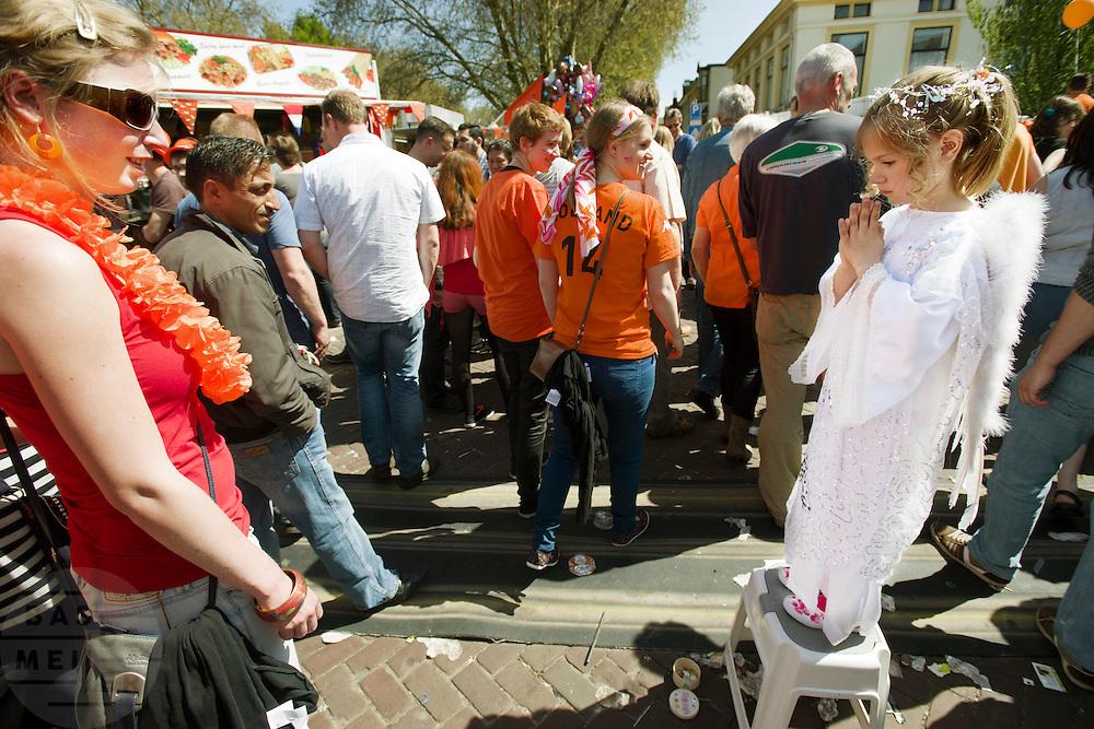 Een meisje staat verkleed als engel op de vrijmarkt in Utrecht tijdens Koninginnedag 2012.<br /> <br /> A girl is playing for angel at the flee market on Queensday in Utrecht.