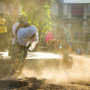 Sweeping the compound courtyard: morning chores in Koumbadiouma. Kolda, Senegal.