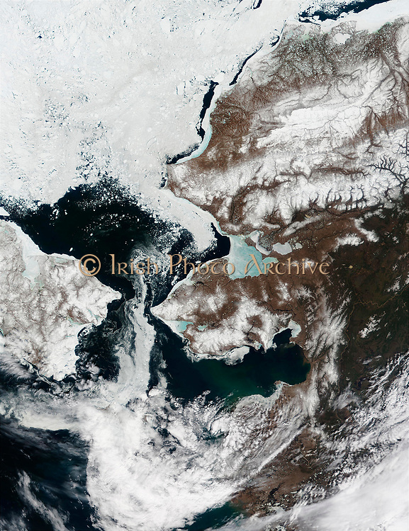 Snow is retreating from the Alaska.s landscape, and the Bering Strait, which separates Alaska's Seward Peninsula (center) from Siberia,is mostly free of ice in this MODIS image from May 22, 2002. Sea ice in the Kotzebue Sound (north of Seward Peninsula) has thinned considerably and now appears sky blue, as the blue reflection of the water shows through from underneath. Sea ice is retreating northward into the Chukchi Sea.