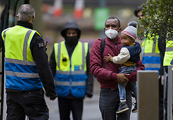 © Licensed to London News Pictures. 16/02/2021. London, UK. A passenger is surrounded by security guards as he carries his child on arrival for quarantine at a Holiday Inn hotel near Heathrow Airport for the second day. People entering the UK from a 'red list' of 33 high risk countries will have to quarantine at hotels for 10 days to try and stop new coronavirus variants entering the country. Photo credit: Peter Macdiarmid/LNP