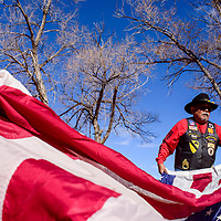 Willie Thomas unfurls a large American flag as he and other members of Veterans Helping Veterans prepare for a ceremony to retire old and tattered flags in Thoreau Friday.