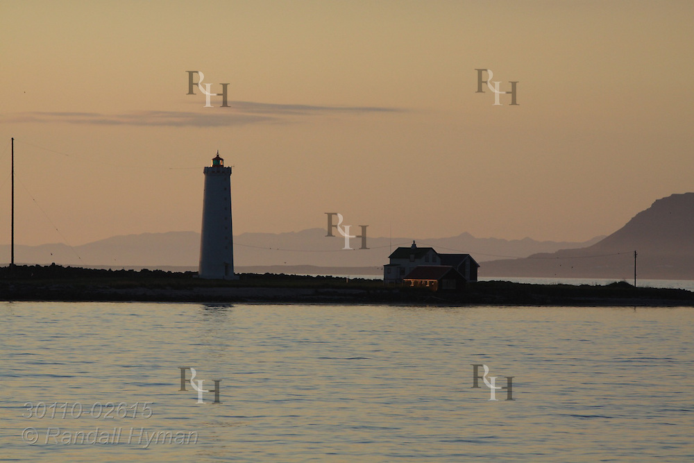 Dusky sky silhouettes lighthouse on Seltjarnarnes coast in midsummer; Reykjavik, Iceland.