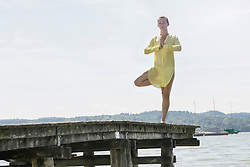 Woman doing tree pose yoga on jetty at the lake, Ammersee, Upper Bavaria, Germany