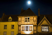 Full moon shining on ancient Medieval architecture along Burford High Street at night, The Cotswolds