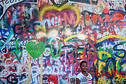 A woman gets a portrait at The Lennon Wall or John Lennon Wall, which is a wall in Prague, Czech Republic. Once a normal wall, since the 1980s it has been filled with John Lennon-inspired graffiti and pieces of lyrics from Beatles songs.