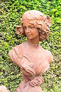 Rusted metal cast iron bust statue female figure, The Walled garden plant nursery, Benhall, Suffolk, England, UK