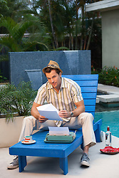 retro feel of a man relaxing on a lounge chair by a pool with a typewriter and bottle of vodka