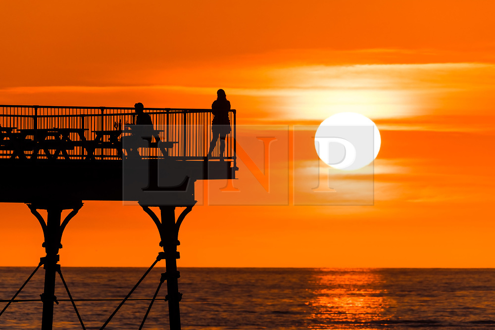 © Licensed to London News Pictures. 28/03/2019. Aberystwyth, UK. 28/03/2019. A beautiful sunset, at the end of another day of warm spring sunshine, silhouettes people on the seaside pier enjoying  the warm evening  in Aberystwyth, on the Cardigan Bay coast of west Wales. High pressure continues to dominate the weather for much England and Wales, with settled conditions forecast to last at least another day , before more cooler conditions return. Photo : Keith Morris/LNP