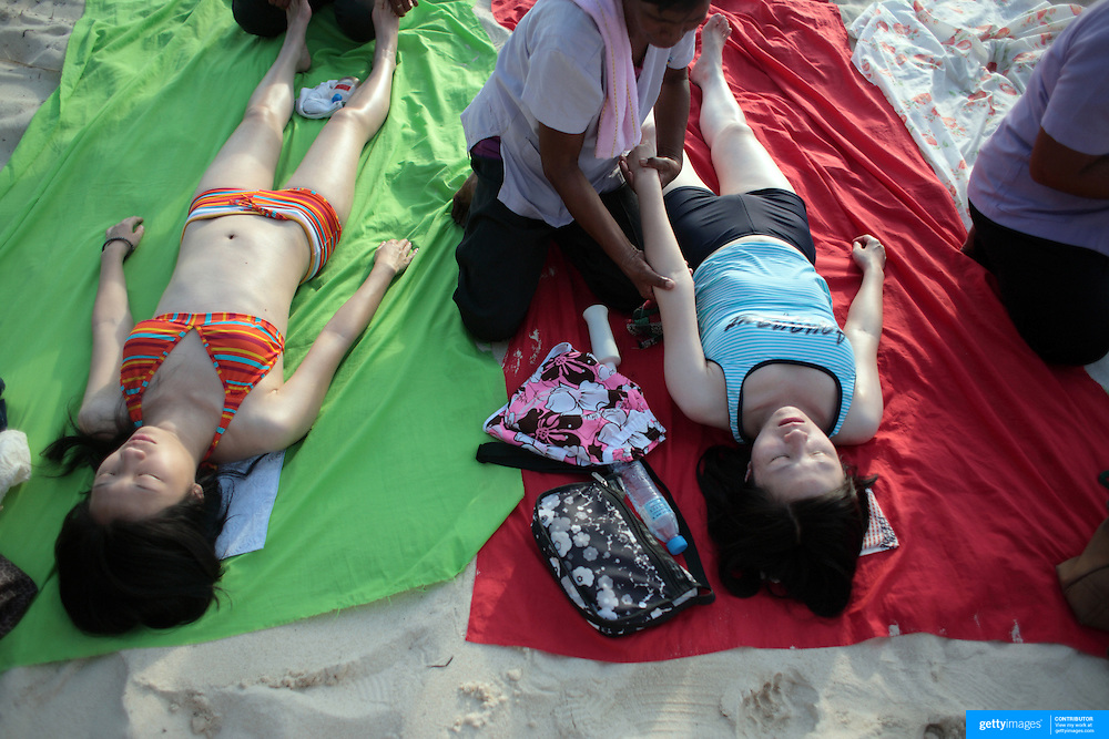 Asian tourists enjoy a massage on White Beach, Boracay Island, the Philippines on October 6, 2008, Photo Tim Clayton..Asian tourists at White Beach, Boracay Island, the Philippines...The 4 km stretch of White beach on Boracay Island, the Philippines has been honoured as the best leisure destination in Asia beating popular destinations such as Bali in Indonesia and Sanya in China in a recent survey conducted by an International Travel Magazine with 2.2 million viewers taking part in the online poll...Last year, close to 600,000 visitors visited Boracay with South Korea providing 128,909 visitors followed by Japan, 35,294, USA, 13,362 and China 12,720...A popular destination for South Korean divers and honeymooners, Boracay is now attracting crowds of tourists from mainland China who are arriving in ever increasing numbers. In Asia, China has already overtaken Japan to become the largest source of outland travelers...Boracay's main attraction is 4 km of pristine powder fine white sand and the crystal clear azure water making it a popular destination for Scuba diving with nearly 20 dive centers along White beach. The stretch of shady palm trees separate the beach from the line of hotels, restaurants, bars and cafes. It's pulsating nightlife with the friendly locals make it increasingly popular with the asian tourists...The Boracay sailing boats provide endless tourist entertainment, particularly during the amazing sunsets when the silhouetted sails provide picture postcard scenes along the shoreline...Boracay Island is situated an hours flight from Manila and it's close proximity to South Korea, China, Taiwan and Japan means it is a growing destination for Asian tourists... By 2010, the island of Boracay expects to have 1,000,000 visitors.