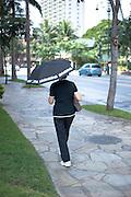 A woman walking through Waikiki with an umbrella.