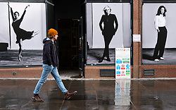 Glasgow, Scotland, UK. 12 March 2021. On the day Covid-19 lockdown is relaxed slightly in Scotland the city centre streets in Glasgow city centre remain almost deserted virtually all shops ad cafes are still closed. Pic;  Man walls past billboards of female models on shopfront of new shop being refurbished for opening. Iain Masterton/Alamy Live News