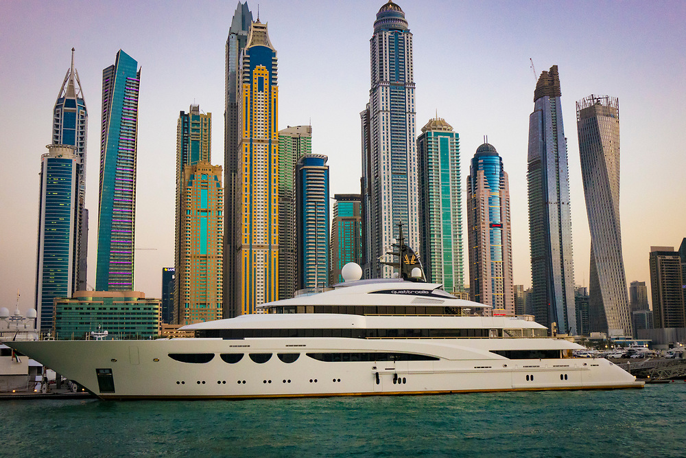 The luxurious Quattroelle Yacht in Dubai at sunset with some of the unique skyscrapers in the background.