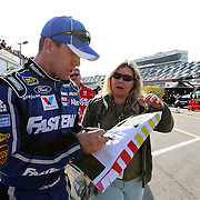 NASCAR Sprint Cup driver Carl Edwards (99) is seen signing an autograph in the pits during the practice session prior to the NASCAR Sprint Unlimited Race at Daytona International Speedway on Saturday, February 16, 2013 in Daytona Beach, Florida.  (AP Photo/Alex Menendez)