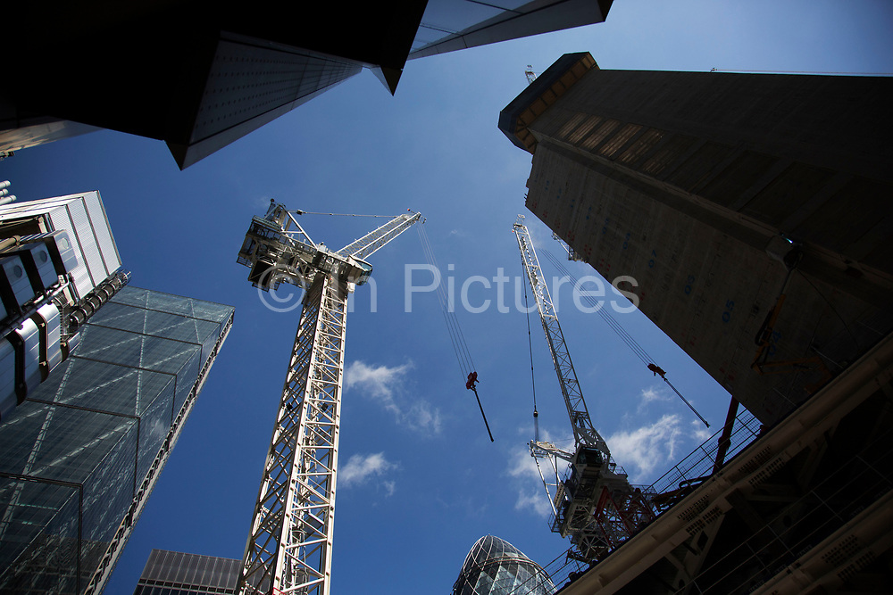 High rise skyscraper construction underway using cranes in the heart of the City of London, United Kingdom. An increasing amount of tall buildings has transformed the skyline of the City over the years, each one adding to the view above as modern architecture reaches for the sky in close proximity.
