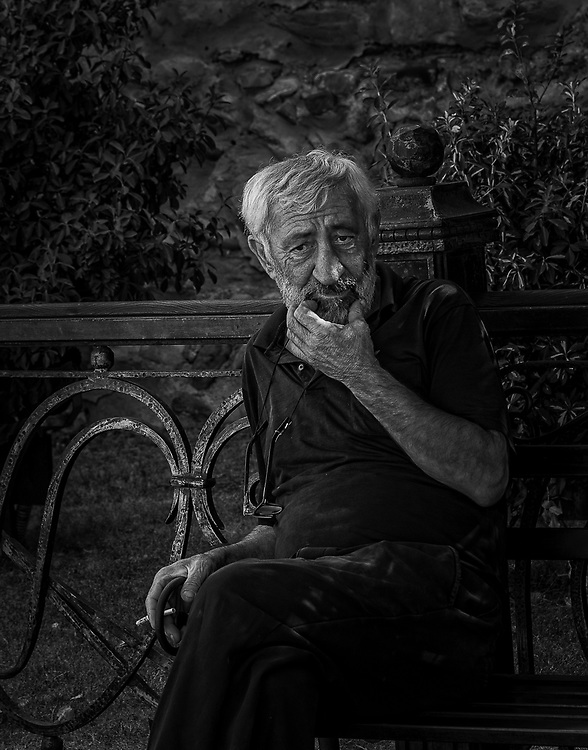 Portrait of a thoughtful man sitting on a bench smoking a cigarette