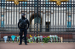 © Licensed to London News Pictures. 09/04/2021. LONDON, UK. A police officer in front of flowers left by well wishers outside Buckingham Palace after the death of Prince Philip, aged 99, was announced.  Photo credit: Stephen Chung/LNP