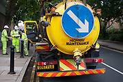 Highway maintenance workers and their vehicle working in London. This water truck inspecting pipelines in the road has a large blue sign with a white arrow to direct other road users aroud the wide vehicle.