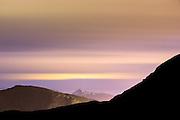 silhouette of montain in the front, with montain landscape and colorful sky   Silhuett fra ryggen av Teigetua i front, Leinehornet til venste, med fargerik himmel.
