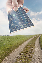 Person's hand holding business card depicting as solar panel, Bavaria, Germany