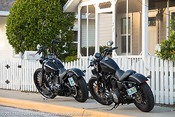 One way to avoid a ticket - don't park in front of a yellow line! Two Harley-Davidsons just off Main Street during Daytona Beach Bike Week. FL. USA. Saturday March 11, 2017. Photography ©2017 Michael Lichter.