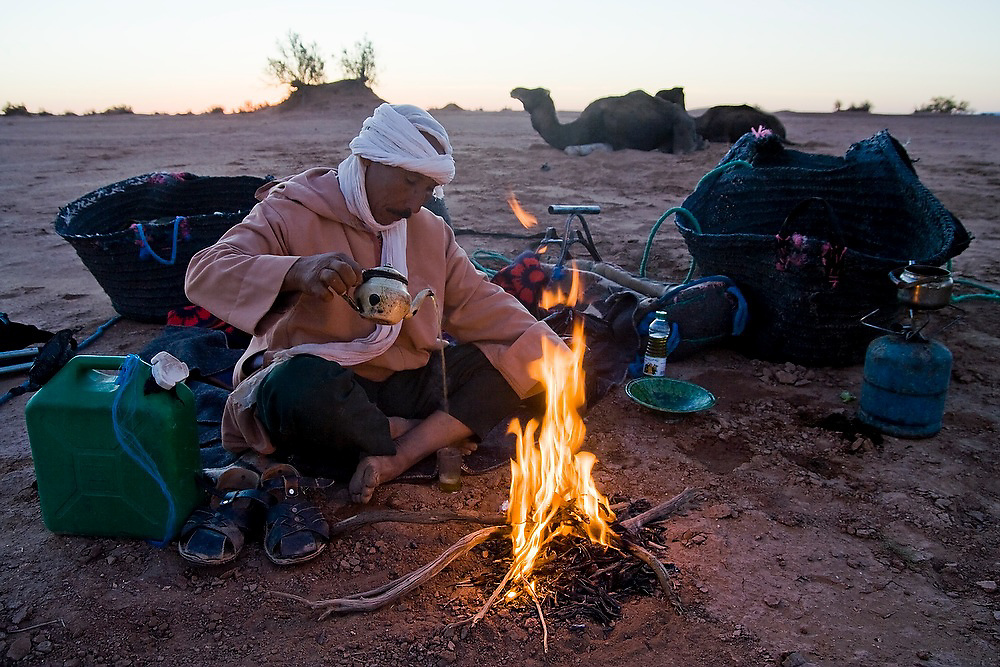 Camel guide Elhussein Sbiti pours mint tea from a tea kettle as he sits near a campfire on a three-day camel trek to the remote sand dunes of Erg Zehar, near M'hamid in the Moroccan Sahara. Sbiti, like many berber nomads in the region, has found opportunity in the new tourism trade burgeoning since the settling of tensions between Morocco and neighboring Algeria..