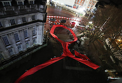 A 45-metre red ribbon is unfurled during a candlelit vigil for World Aids Day, in Spring Gardens, London.